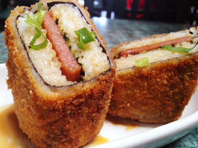 Spam musubi is a popular snack and lunch food in Hawaii composed of a slice of grilled Spam on top of a block of rice, wrapped together with nori dried seaweed CT