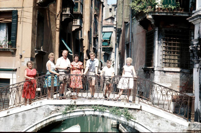 A family poses for a picture on a bridge in Venice.
