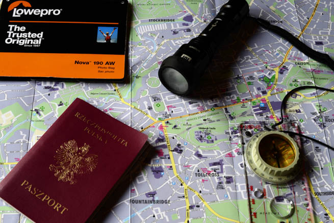 A passport and travel tickets sit atop a map.