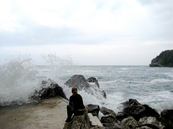 Woman watches waves crash on rocky shore in Iceland.