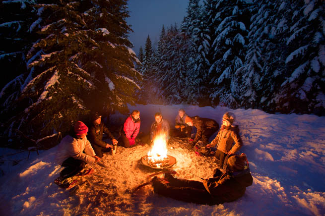 A group of people gather around a fire pit during a snowy evening in Vermont.