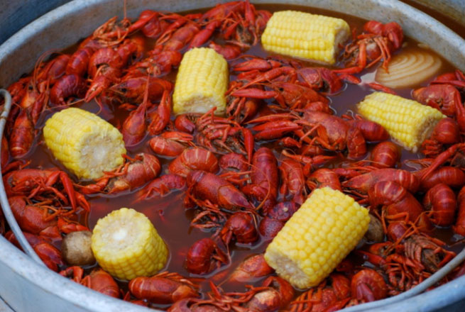 A pot of crawfish and corn on the cob waits to be eaten.